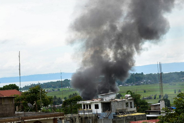 ANOTHER FIRE. Black smoke billows from burning houses near the Lanao del Sur provincial capitol in Marawi. Photo by Ted Aljibe/AFP