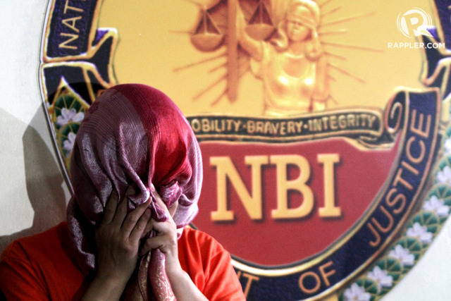 BANK FRAUD. Bank officer Maria Victoria Lopez uses a scarf to hide her face at an NBI news briefing on the Metrobank internal fraud case on July 21 2017. Photo by Inoue Jaena/Rappler