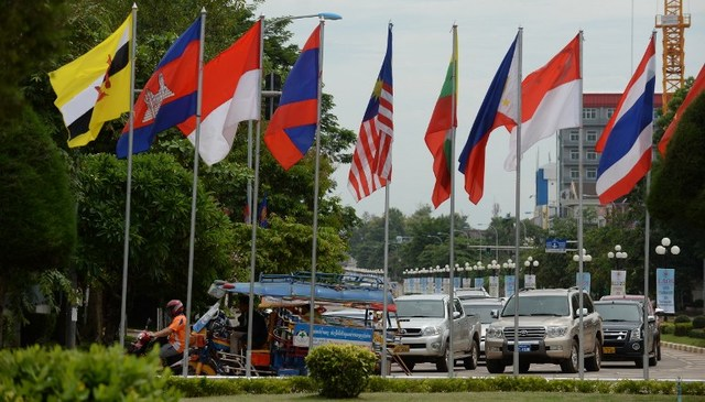 LOCAL TRANSPORT. Cars and tuk-tuk ride past a row of ASEAN member countries' flags in the Laos capital of Vientiane on July 23, 2016. Photo by Hoang Dinh Nam/AFP