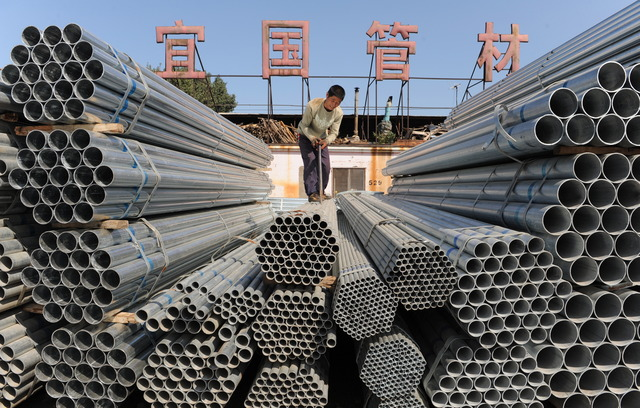 INCREASED OUTPUT. Workmen load steel tubes in a metals wholesale market in Shenyang, China on September 18, 2009. File photo by EPA